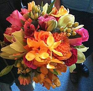 Tropical wedding bridal bouquet in pinks and oranges - roses, orchids, dahlias, green hypericum, asiatic lilies