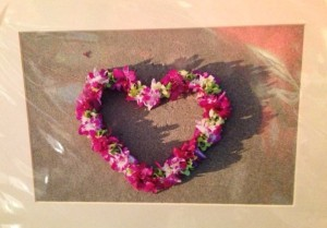 Heart made of flowers lying on beach - print